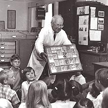 Harbison showing a class of 1st graders entomology specimens. Photo originally shot for a copy of Environment Southwest, 1968.